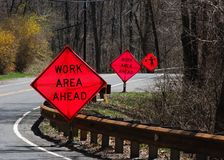 Road Work warning  on a Curve. Signs along a curved road advising that there is a work area ahead Royalty Free Stock Images