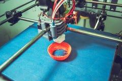 Work 3d printer close. Printing 3D printer Object Orange plastic On blue background. Plastic Wire Filament, Modern printing technology. Progressive additive stock images
