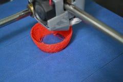 Work 3d printer close. Printing 3D printer Object Orange plastic On blue background. Plastic Wire Filament, Modern printing technology. Progressive additive royalty free stock images