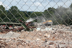 Work on Demolition Site. Demolition work site being viewed through a chain link fence royalty free stock photo