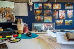 Work desk with  beautiful photos of tourist attractions on the partition stock image