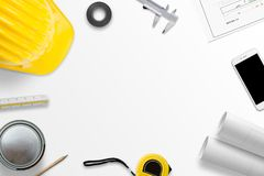 Work desk on construction site. Tools, measuring instruments and projects on white desk. Flat lay royalty free stock images