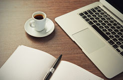 Work desk with a cup of coffee computer laptop, notebook, pen Royalty Free Stock Image
