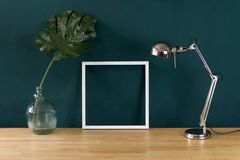 Work desk decorated with white photo frame and tropical monstera leaf stock photography