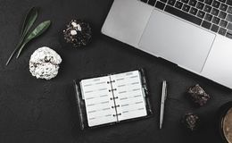Work desk, laptop and work planbook, sweets and milk coffee for break. Top view, flat lay Royalty Free Stock Photos