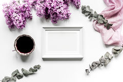 Work desk with lilac flowers, frame and coffee in home office on white background top view space for text. Female work desk with lilac flowers, frame and coffee stock photo