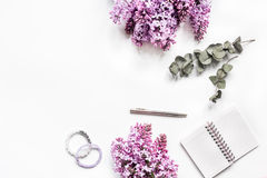 Work desk with lilac flowers in home office on white background top view space for text stock image