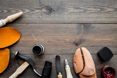 Work desk of shoemaker with instruments, wooden shoe and leather. Dark wooden background top view copy space. Work desk of shoemaker with instruments, wooden royalty free stock image