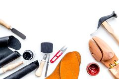 Work desk of shoemaker with instruments, wooden shoe and leather. White background top view copy space. Work desk of shoemaker with instruments, wooden shoe and royalty free stock photos