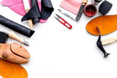 Work desk of shoemaker with instruments, wooden shoe and leather. White background top view copy space. Work desk of shoemaker with instruments, wooden shoe and royalty free stock images