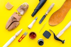 Work desk of shoemaker with instruments, wooden shoe and leather. Yellow background top view.  stock photo