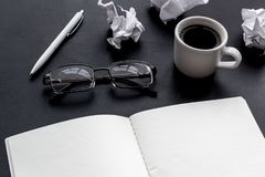 Work desk of writer with notebook, glasses, coffee on black background mock up. Work desk of writer with notebook, glasses, coffee on black desk background mock stock images