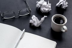 Work desk of writer with notebook, glasses, coffee on black background mock up. Work desk of writer with notebook, glasses, coffee on black desk background mock stock photos
