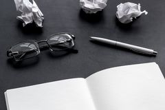 Work desk of writer with notebook, glasses, pen on black background mock up. Work desk of writer with notebook, glasses, pen on black desk background mock up royalty free stock photos
