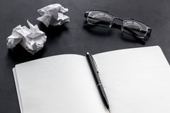 Work desk of writer with notebook, glasses, pen on black background mock up. Work desk of writer with notebook, glasses, pen on black desk background mock up stock photo