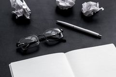 Work desk of writer with notebook, glasses, pen on black background mock up. Work desk of writer with notebook, glasses, pen on black desk background mock up royalty free stock image