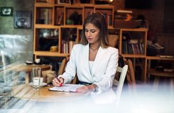 Work and document. Young business woman writing on document at cafe royalty free stock photos