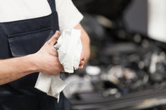 Work is done. Close-up of mechanic wiping his hands with handkerchief while standing in front of the car stock photo