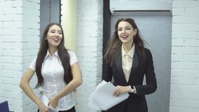 Business people working in office. The work is done. Happy positive workers of large business center - two pretty women in formal costume happily toss up papers stock video footage