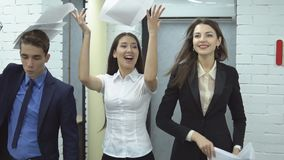 Business people working in office. The work is done. Happy positive workers of large business center - two pretty women and man in suit happily toss up papers stock video footage