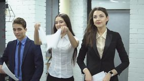 Business people working in office. The work is done. Happy positive workers of large business center - two pretty women and man in suit toss up papers rejoicing stock video footage