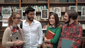Work is Done. Smiling students discussing successfully accomplished project work, two young men and women standing before library bookshelves, holding books and stock footage