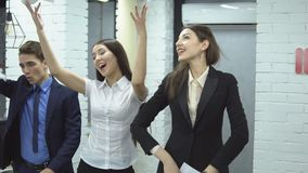 Business people working in office. The work is done. two young women and man in suit toss up papers rejoicing at the completed work, slow motion stock footage