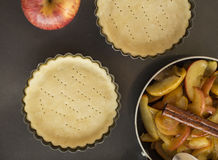 Work with the dough. Form for baking and ingredients for apple pie. Stock Photo