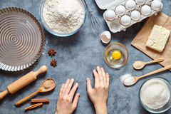 Work with the dough. The kitchen table raw ingredients, the woman`s hand ready to knead the preparing cake Royalty Free Stock Photo
