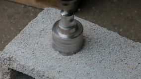 Work with a drill bit with a nozzle. Specialist drilled a hole for mounting socket stock video