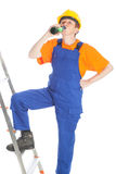 Work and drink. Portrait of a female builder with a yellow helmet and a blue bib overall standing on a ladder and drinking a bottle of beer in front of a white royalty free stock photo