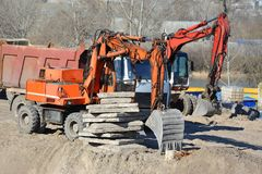 Excavating machine on construction site. Work of excavating machine on building construction site stock image