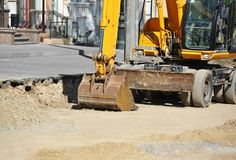 Excavating machine on road site. Work of excavating machine on road construction site royalty free stock images