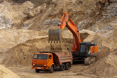 The work of excavator in his career. Sand quarry excavator load sand dump truck Royalty Free Stock Photos