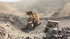 The excavator and dumper in the quarry, Large yellow excavator loaded ore into a dumper, Industrial exterior