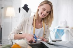 Joyful female dressmaker conducting measurement. Work with fabric. Glad female dressmaker working with fabric and using scissors Royalty Free Stock Photos