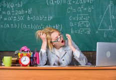 Work far beyond actual school day. Teacher busy with paperwork. Teacher tired face keep work after classes. Workaholic. Sleepy at workplace. Teacher woman sit royalty free stock photo
