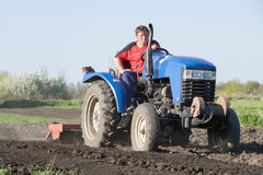 The work of a farmer in the spring. A farmer on a tractor lands a vegetable garden in the spring Royalty Free Stock Photography