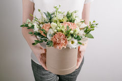 Work florist, bouquet in a round box. smelling flowers holding peach roses  in hat  against the plastered wall. Royalty Free Stock Photos