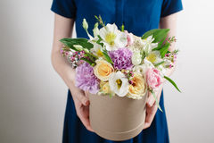 Work florist, bouquet in a round box. smelling flowers holding peach roses in hat against the plastered wall. Stock Photography