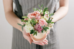 Work florist, bouquet in a round box. smelling flowers holding peach roses in hat against the plastered wall. Stock Photos