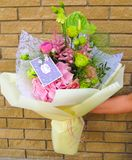 The work of a florist in a flower shop - a bright bouquet with a greeting card stock image