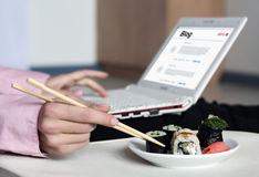 Work and Food Woman working on Laptop taking Sushi. Asian Sushi Set and Woman working on Laptop Computer taking Food Roll with wooden Chopsticks royalty free stock image