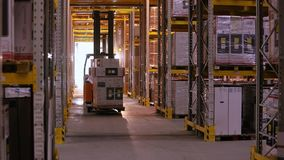Work forklifts in the warehouse. Forklift with boxes rides between the rows in the warehouse. Industrial interior