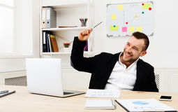 Work with fun, successful businessman at workplace. Working with fun. Smiling successful businessman in formal wear sitting at workplace in modern office and royalty free stock photography