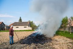 Work in the garden. Farmer burning dried branches royalty free stock photos