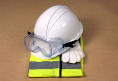 Work Gear. Yellow hi vis vest with hard hat, gloves and safety goggles royalty free stock images