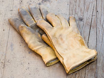 Work Gloves. A pair of work gloves lying on planks of wood Stock Photos