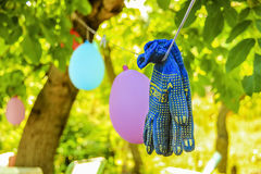 Work gloves hanging on the rope. On the background of greenery Royalty Free Stock Photography
