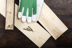 Work gloves on planks on dark brown wooden background, on table in workshop. Space for text royalty free stock image